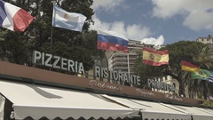 Italian pizzeria sign city slow motion with flags Stock Footage