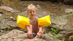 Little Blond Girl in Arm-hands Sits Touches Feet on Stone Stock Footage