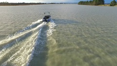 Aerial shot of young man wake boarding behind a motorboat in a lake, slow motion Stock Footage