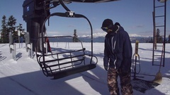 A young man snowboarder riding the chairlift up the mountain, super slow motion. Stock Footage