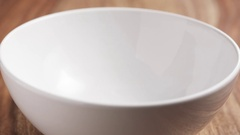Slow motion chocolate crunchy balls for breakfast falling into white bowl Stock Footage