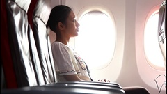 Young woman watching the monitor in a flying aircraft Arkistovideo