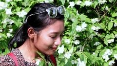 Girl sniffs a flower meadow Stock Footage