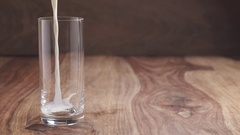 Slow motion of pouring milk into the glass on wood table with copy space Stock Footage