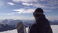 A young man snowboarder walking with his board on a scenic snow covered mountain Stock Footage