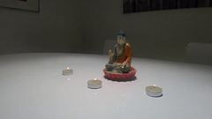 Statue of Buddha on white table with 3 candles Stock Footage