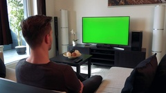 A man watches a TV with a green screen in a cozy living room Stock Footage
