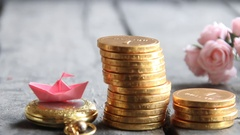 Start up business concept. Stacks of golden coins and a paper boat Stock Footage