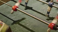 Friends playing a game of table football in a club Stock Footage