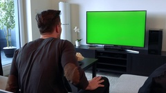 A man cheers and gesticulates excitedly at a TV with a green screen Stock Footage