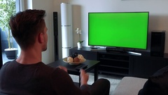A man watches a TV with a green screen in a cozy living room and begins to Stock Footage