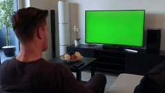 A man screams and gesticulates angrily at a TV with a green screen Stock Footage