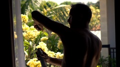 Silhouette of man applying anti-perspirant on armpit standing on terrace Stock Footage