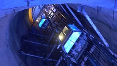 Elevators for people who climb and descend through a shaft deep illumi Arkistovideo