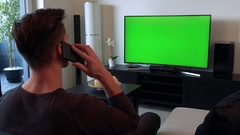 A man talks on a smartphone and watches a TV with a green screen Stock Footage
