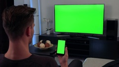 A man turned with the back of his head to the camera watches a TV and eventually Stock Footage