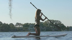 A young woman sup stand-up paddleboarding on her knees on a lake. Stock Footage