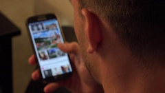 A man, turned with the back of his head to the camera, swipes on a smartphone Stock Footage