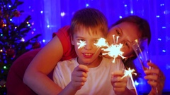 Happy family lit sparklers at the party. In the background, bokeh lights and Stock Footage