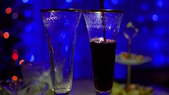 Red wine is poured into glasses. In the background, bokeh lights and garlands of Stock Footage