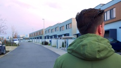 A man is turned with the back to the camera and looks around a neighborhood Stock Footage