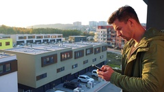 A young, handsome man types on his smartphone on a balcony, eventually looks out Stock Footage