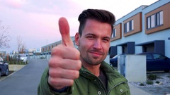 A young, handsome man stands on a road and shows a thumb up to the camera, a Stock Footage