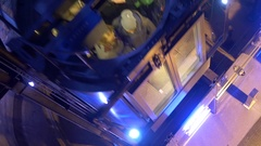 Lifts people moving through a shaft deep illuminated with blue light Stock Footage