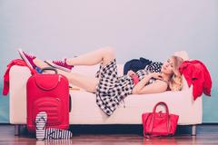 Young woman packing suitcase on sofa Kuvituskuvat