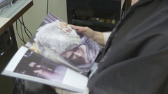 Girl leafing through a magazine at the hairdresser Stock Footage