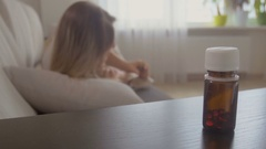 Young woman felling sick caughing in bed and taking pills from bedside table Stock Footage