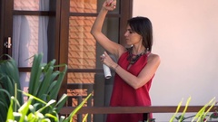 Young woman applying deodorant on her armpit standing on terrace, slow motion Stock Footage