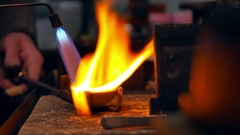 Goldsmith melting gold to liquid state in crucible with gasoline burner Stock Footage