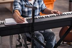Handicapped musician writing down notes Stock Photos