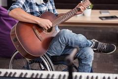 Handicapped devoted musician playing guitar Stock Photos