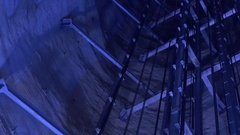 Lift of people moving through a deep well lit with blue light Stock Footage