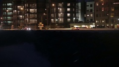 Waves crash storm barrier, traffic apartment buildings, Reykjavik Iceland night  Stock Footage