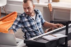 Handicapped musician using his laptop Stock Photos