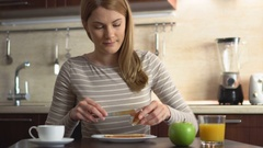 Beautiful young making bread and butter with jam. Breakfast with juice and Stock Footage