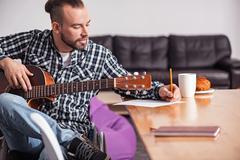 Talented handicapped guy writing song lyrics Stock Photos