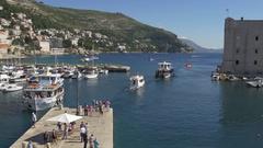 Tourist boat landing on Dubrovnik old port pier Stock Footage