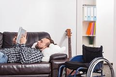 Young handicapped man lying on a sofa Stock Photos