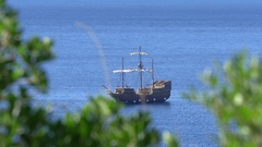 Reconstructed old sailing ship seen throug tree leaves Stock Footage