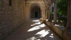 Tracking shot through archway of old Benedictine monastery on Lokrum Stock Footage