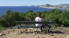 Woman relaxing on park bench on Lokrum island with view to Dubrovnik Stock Footage