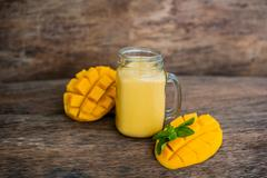 Mango smoothie in a glass Mason jar and mango on the old wooden background... Stock Photos