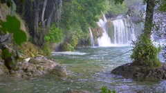 Enrooted tree in front of waterfall in Krka national park Stock Footage