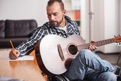 Handicapped musician writing down music chords Stock Photos