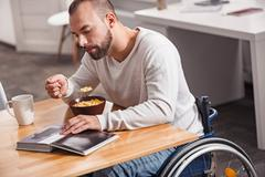 Intelligent disabled man looking through book in the morning Stock Photos