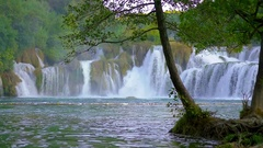 Tree trunk and root in front of big waterfall in Krka national park Stock Footage